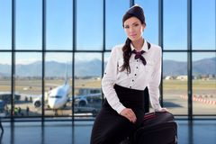 Estate, vacanza e concetto di viaggio - hostess con la valigia in aeroporto fotografia stock