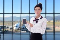 Estate, vacanza e concetto di viaggio - Smart Phone della tenuta dell'hostess con lo schermo in bianco in aeroporto fotografia stock