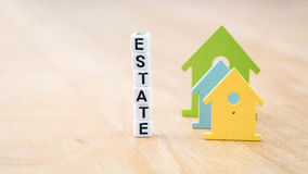 ESTATE word of cube letters behind coloured house symbols on wooden surface. Concept Royalty Free Stock Photos
