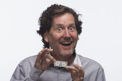 Estatic man holding dollar bill, horizontal. Happy man holding a dollar bill against white background, horizontal Royalty Free Stock Images