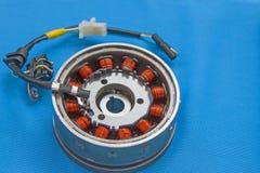 Estator de la rueda volante del magneto del equipo en un fondo azul fotografía de archivo libre de regalías