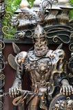 Estatua adornada del metal de un caballero en los brazos foto de archivo