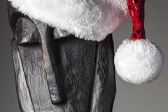 Estatua africana con el sombrero de Papá Noel Foto de archivo libre de regalías