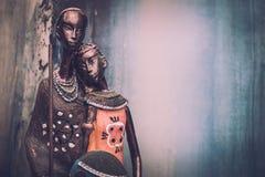 Estatua africana de una muchacha con los hombres jovenes del azul étnico con el fondo ocre detrás Imagen de archivo libre de regalías