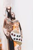 Estatua africana de una muchacha con los hombres jovenes del azul étnico con el fondo ocre detrás Imagenes de archivo