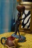 Estatua africana de una muchacha con un pote en su cabeza con un origen étnico detrás Fotos de archivo libres de regalías