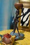 Estatua africana de una muchacha con un pote en su cabeza con un origen étnico detrás Imagen de archivo