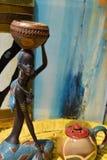Estatua africana de una muchacha con un pote en su cabeza con un origen étnico detrás Fotos de archivo
