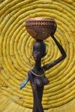 Estatua africana de una muchacha con un pote en su cabeza con un origen étnico detrás Fotografía de archivo