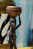 Estatua africana de una muchacha con un pote en su cabeza con un origen étnico detrás Foto de archivo