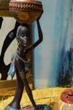 Estatua africana de una muchacha con un pote en su cabeza con un origen étnico detrás Imagenes de archivo