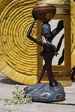 Estatua africana de una muchacha con un pote en su cabeza con un origen étnico detrás Foto de archivo libre de regalías