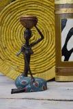 Estatua africana de una muchacha con un pote en su cabeza con un origen étnico detrás Imágenes de archivo libres de regalías
