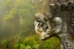 Estatua antigua del dragón de la fantasía en un bosque imagenes de archivo