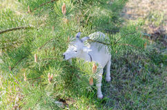 Estatua artificial de la cabra cerca del pino Foto de archivo