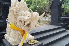Estatua blanca del Balinese en la entrada al templo en un día nublado foto de archivo
