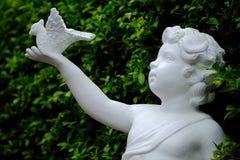 Estatua blanca del cupido con el pájaro Imagen de archivo