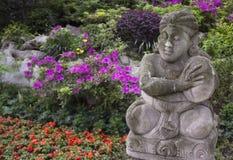 Estatua china del jardín delante de las flores Fotos de archivo