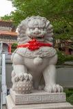 Estatua china del león con la cinta roja Fotografía de archivo libre de regalías