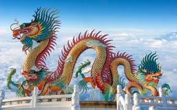 Estatua colorida del dragón con el cielo azul y las nubes Foto de archivo