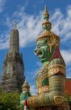 Estatua con el fondo de Temple of Dawn, Tailandia del guarda Imagenes de archivo