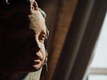 Estatua con la cara del niño con la media cara iluminada fotos de archivo