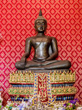 Estatua de bronce de Buda con la pared roja detrás en el templo Foto de archivo libre de regalías