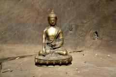 Estatua de bronce de la tierra conmovedora Buda en la madera Fotografía de archivo libre de regalías