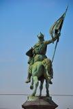 Estatua de bronce de un caballero en su caballo con una bandera en su mano imagenes de archivo