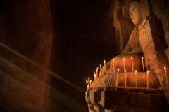 Estatua de Buda dentro de la pagoda con la luz de la vela bajo rayo de la luz Imagenes de archivo
