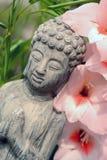 Estatua de Buda en un jardín de flores con la flor rosada Imagenes de archivo