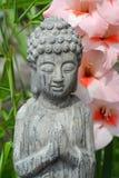 Estatua de Buda en un jardín de flores con la flor rosada Foto de archivo
