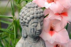Estatua de Buda en un jardín de flores con la flor rosada Fotografía de archivo