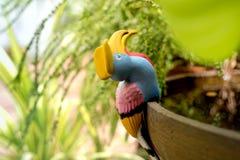 Estatua de cerámica colorida del pájaro en los potes del agua en el jardín Foto de archivo libre de regalías
