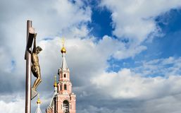 Estatua de la crucifixión y de la iglesia. Fotos de archivo