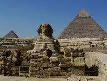 Estatua de la esfinge de El Cairo con las pirámides y el terraplén detrás Imágenes de archivo libres de regalías