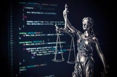 Estatua de la justicia con código en el dispositivo del monitor en fondo imagen de archivo libre de regalías
