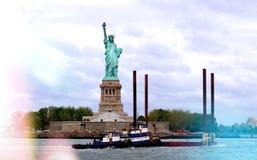 Estatua de la libertad con el barco colorido que pasa cerca fotos de archivo