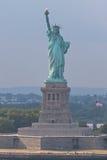 Estatua de la libertad con el indicador americano imagenes de archivo