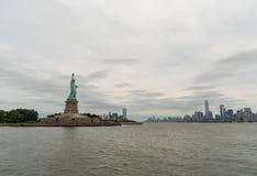Estatua de la libertad, de Manhattan más baja, y de Jersey City visto del agua Imagenes de archivo