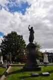 Estatua de la silueta de Angel Pointing Up en un paisaje del cementerio fotos de archivo