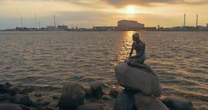 Estatua de la sirena en orilla del agua de la ciudad en la puesta del sol almacen de metraje de vídeo