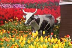 Estatua de la vaca con los tulipanes Imagenes de archivo