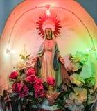 Estatua de la Virgen María iluminada por diversos colores Fotos de archivo