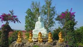 Estatua de mármol de Buda entre las flores en parque contra el cielo