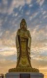 Estatua de oro Buda de Guanyin con el fondo crepuscular del cielo Foto de archivo libre de regalías