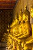 Estatua de oro de Buda en el pedestal con las paredes viejas foto de archivo