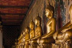 Estatua de oro de Buda en el pedestal con las paredes viejas fotos de archivo