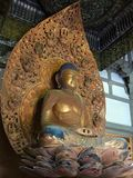 Estatua de oro de Buda que se sienta en loto adentro Byodo-en el templo en Oahu, Hawaii imagenes de archivo