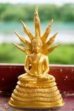 Estatua de oro de Buda con el rey de nagas Imagen de archivo libre de regalías